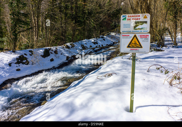 Warning sign by overflow flood channel with snow - Stock Image