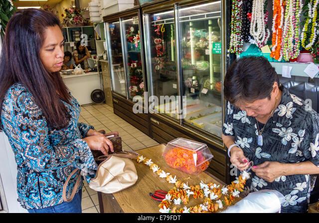 Hawaii Hawaiian Oahu Honolulu Chinatown Kekaulike Street florist shop flower leis refrigerated sale customer Asian - Stock Image