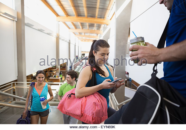 Friends talking and using cell phone at gym - Stock-Bilder