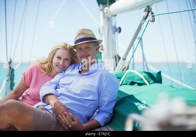 Couple sitting on deck of sailboat - Stock Image