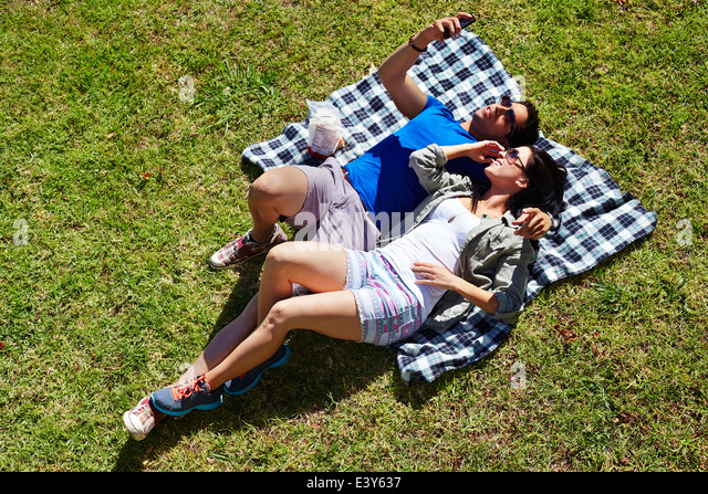 Overhead view of couple taking self portrait on picnic blanket - Stock Image