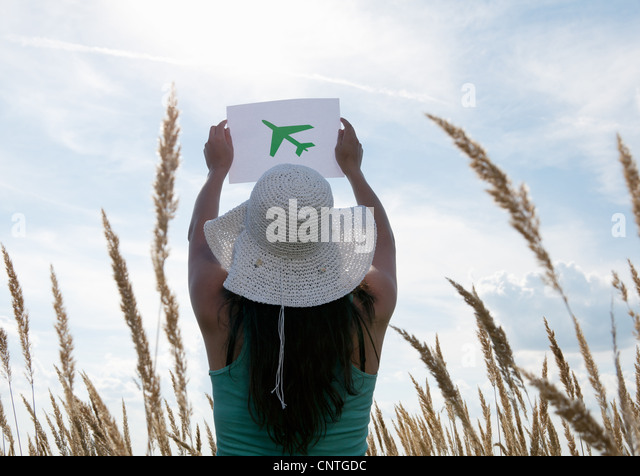 Woman holding picture of airplane in sky - Stock Image