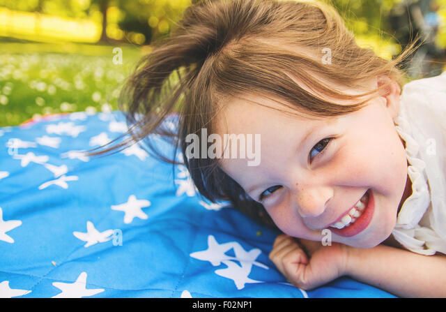 Close-up of a girl lying on a blanket laughing - Stock Image