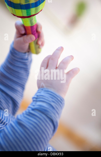 Baby boy playing with rattle, Munich, Bavaria, Germany - Stock Image