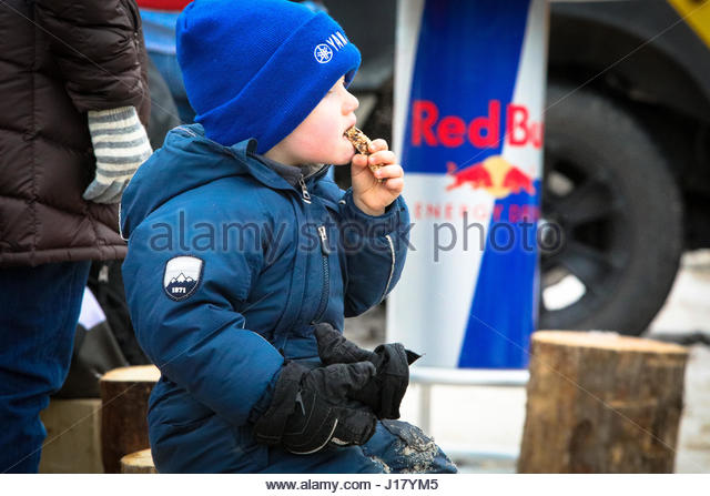 Little boy warming by the fire with a snack - Stock Image