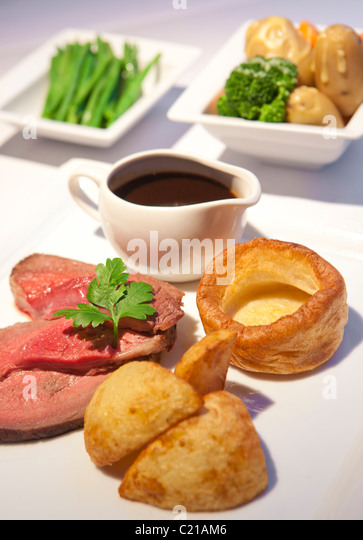 Traditional rare roast beef sunday dinner with vegtables and gravy. - Stock Image