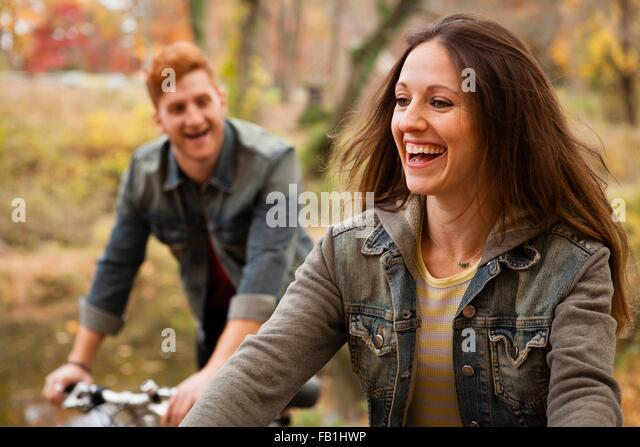 Young couple cycling along riverside in autumn - Stock Image
