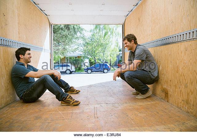 Men talking inside of empty moving van - Stock Image