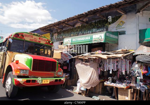 Nicaragua Granada Calle Atravesada shopping market makeshift vendor stall cardboard bus public transportation - Stock Image