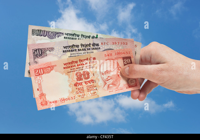 One 20. one 50 and one 100 Indian rupee bills with the portrait of Mahatma Gandhi are held in the hand. Sky is in - Stock-Bilder