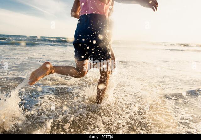 Young man running in sea, low section - Stock Image