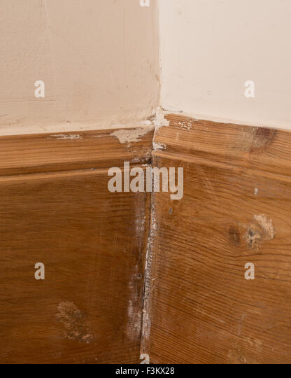 Poor diy workmanship - badly fitted wooden skirting boards with butted joints - Stock Image