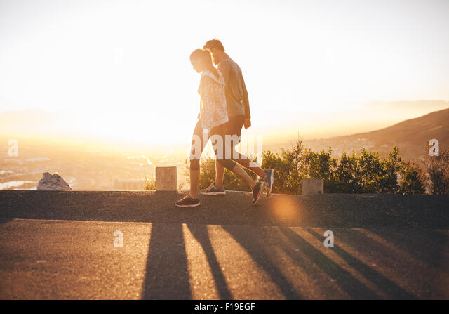 Couple walk along road at sunrise. Couple talking a walk on hillside road with bright sunlight. - Stock Image