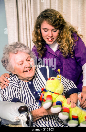 Teen girl visiting and hanging out with elderly old people handicapped handicap woman in assisted care facility - Stock-Bilder