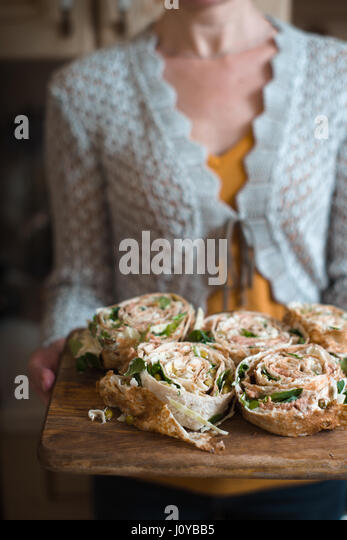 Rolls with tuna and greens on the wooden board in the woman`s hands - Stock Image