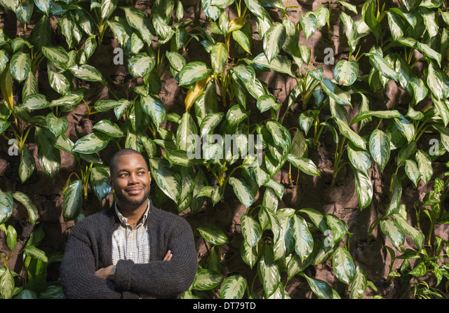 A man standing with folded arms, by a wall covered with foliage. - Stock Image