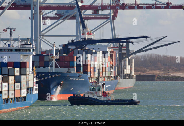 Tug boat assisting container ship by leaving Dunkerque Harbour - Stock Image