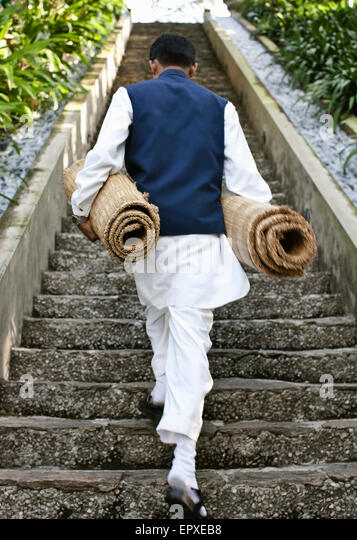 A man carries yoga mats up a staircase to the  open-air pavilion at Ananda in the Himalayas, The Palace Estate, - Stock-Bilder