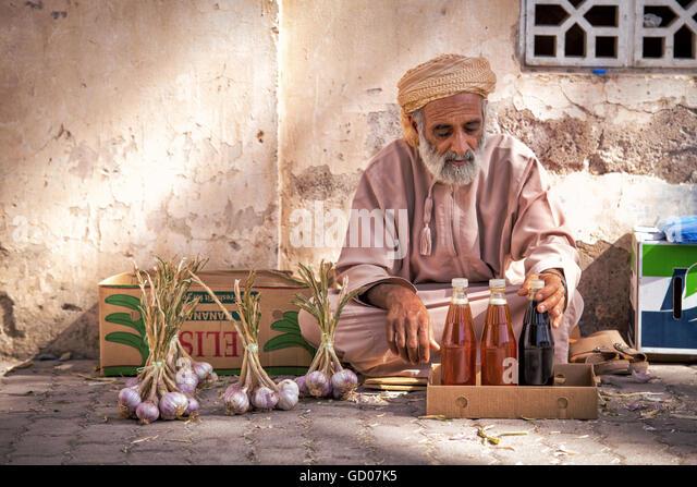 NIZWA, OMAN - APRIL 24 2015:Omani old man selling honey and garlic at the traditional market or souq in Nizwa, Oman - Stock-Bilder