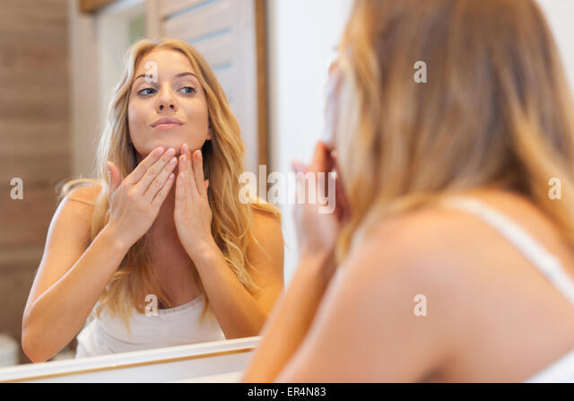 Blonde woman caring about her skin on face. Debica, Poland - Stock Image