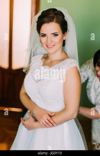 Mother assisting bride in dressing up hotel room before wedding ceremony - Stock Image