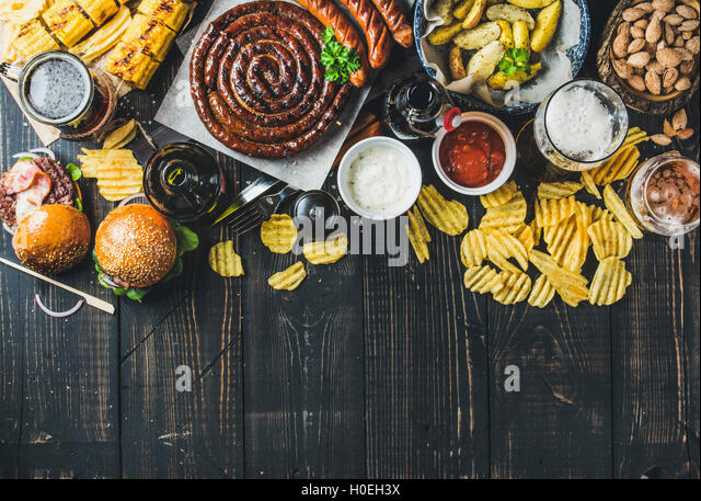 Beer and snack set. Octoberfest food frame concept. Vatiety of beers, grilled sausages, burgers, corn, fried potatoes, - Stock Image