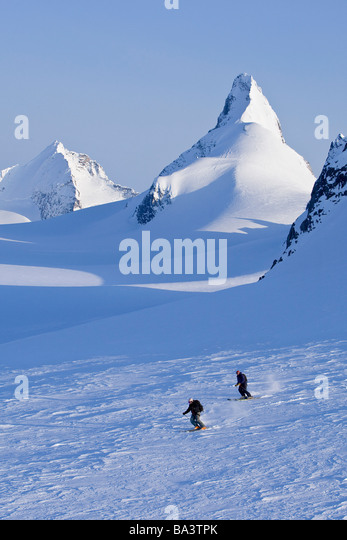Alpine skiers skiing on the Juneau Ice Field and Rhino Peak in the background in Southeast Alaska. Composite - Stock Image