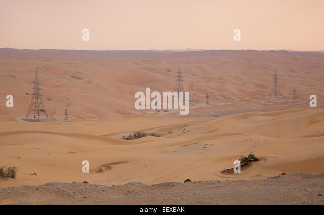 Sand Desert, Arabian Peninsula. Power lines going through desert. - Stock Image