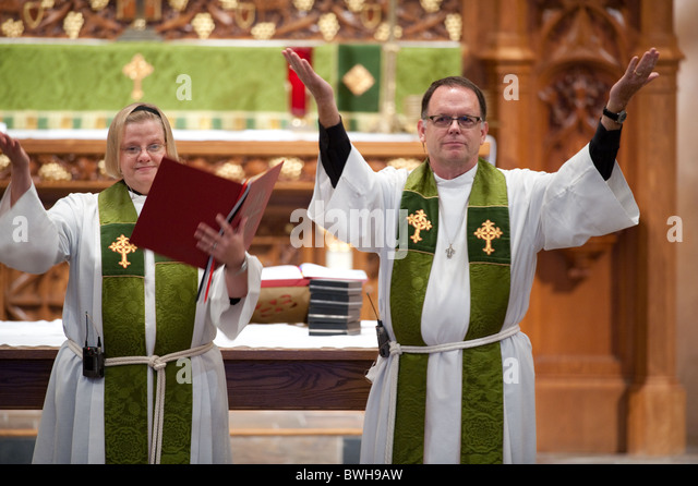 Anglo male minister and Anglo female assisting minister motion for congregation to stand during church service in - Stock Image