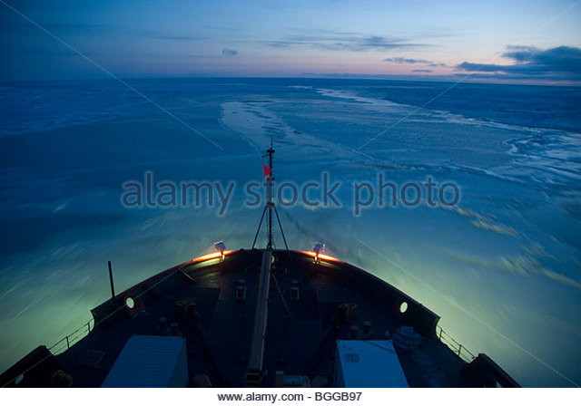 Alaska, Bering Sea. Coast guard icebreaker pushing through new ice before dawn near St. Lawrence Island. - Stock Image