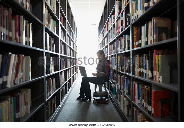 Adult education student researching at laptop between library bookshelves - Stock Image