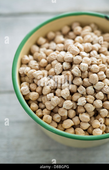 A large bowl of uncooked chickpeas on a rustic wooden table surface. - Stock Image