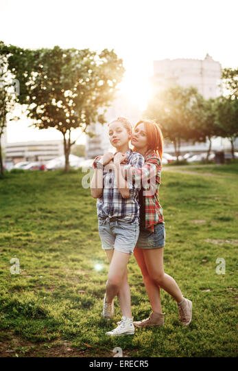 Young Happy Beautiful Best Friends Girls in Pin Up Style Embracing at the Sunset. Friendship Concept. Selective - Stock-Bilder