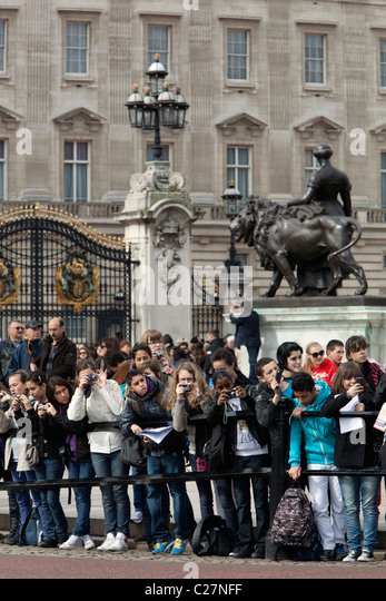 School children watching Changing of the Guard outside Buckingham Palace - Stock Image
