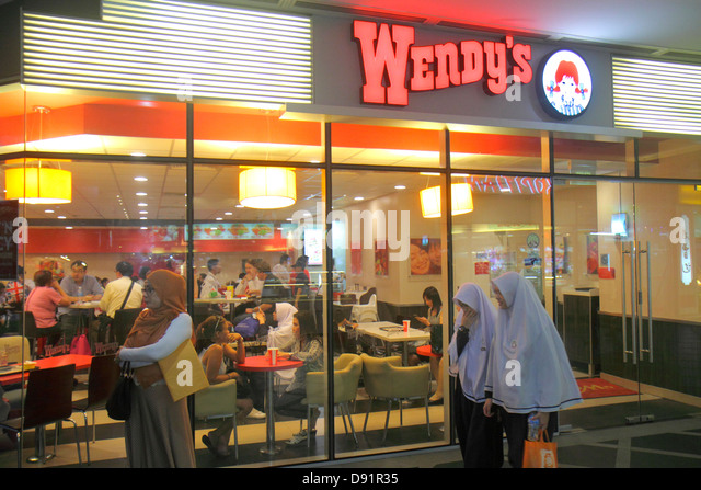 Singapore Kallang Road Wendy's fast food restaurant entrance front Asian woman Muslim hijab - Stock Image