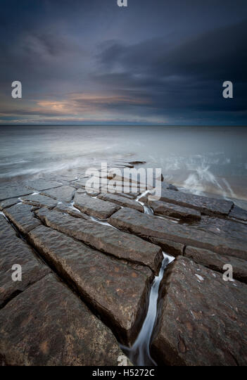 Jigsaw puzzle like slabs of angular rocks leading out into the North Sea off the coast near Berwick upon Tweed on - Stock Image
