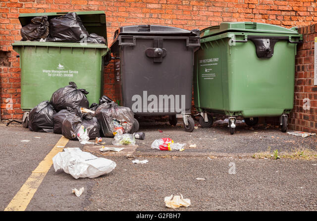 Overflowing commercial dustbins on the street in Hereford, Herefordshire, England, UK - Stock Image