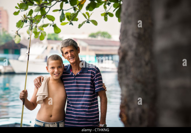 Family portrait with happy boy and grandfather hugging and smiling at camera after fishing near river - Stock Image