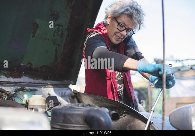 Elderly car mechanic working on her vintage car - Stock-Bilder