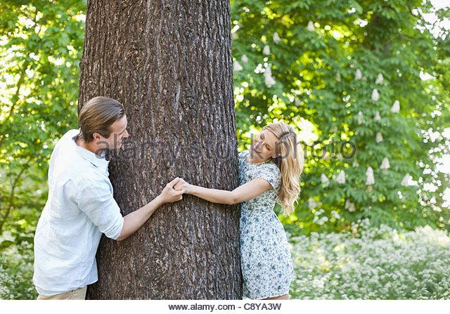 Couple holding hands around tree - Stock-Bilder