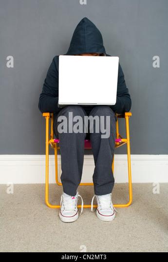 Young man wearing hooded top using laptop - Stock-Bilder