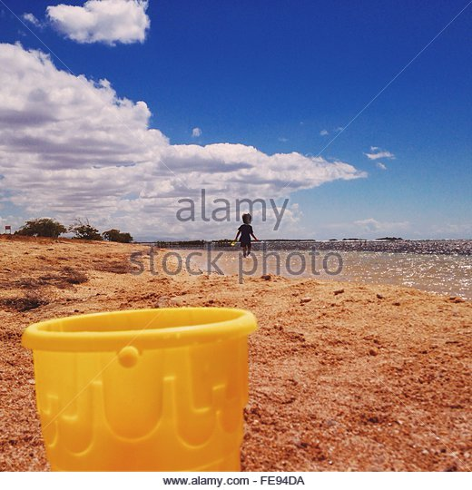 Bucket On Beach And Child Playing In Background - Stock-Bilder