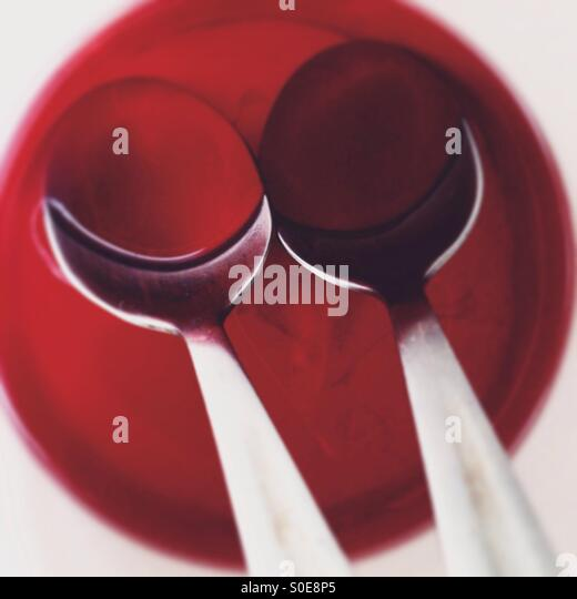 Couple of teaspoon in red juice at white mug - Stock Image