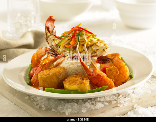 Lobster crab shrimp scallops with asparagus on rice - Stock Image