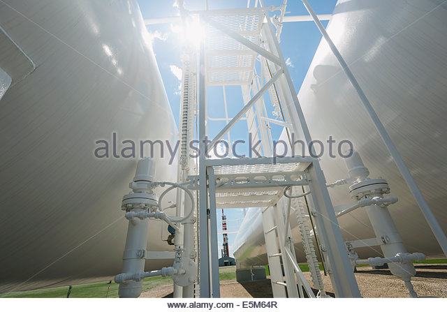 Sun shining over natural gas tanks - Stock Image