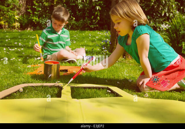 Boy and Girl Painting Cardboard Cut Outs in Garden - Stock Image