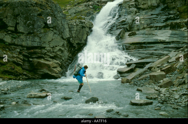 Trekker crossing a stream in the Rapadalen valley, Sarek National Park, Lappland, Norrbottens Län, arctic Sweden. - Stock Image