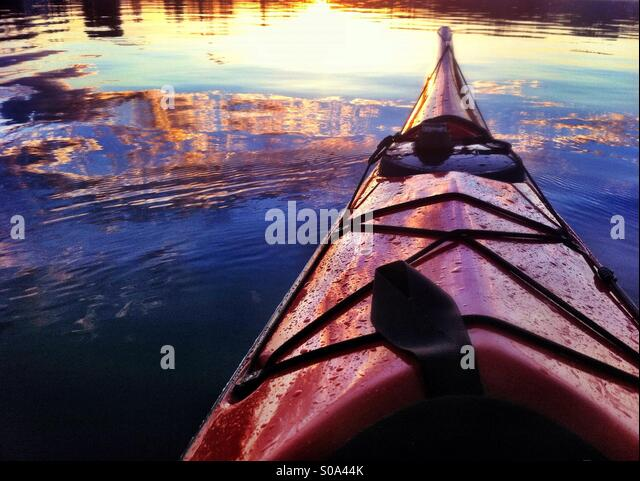 Sunset reflects in the sea water and the bow of red sea kayak - Stock Image