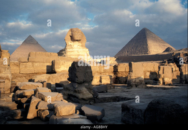 Egypt Sphinx closeup lion paws day pyramids clouds in background - Stock Image