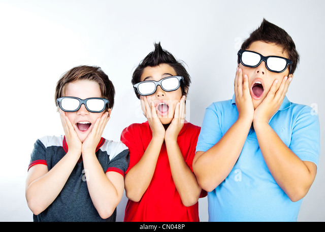 Preteen boys having fun, wearing 3D movie glasses and watching cinema, crazy facial expression, surprised kids - Stock Image